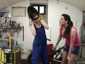 Horny babes have a lesbian moment in a garage