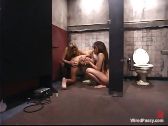 Petite brunette gets dominated by two girls in a restroom