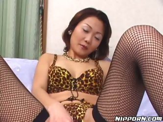 Sex hungry Japanese mature sits on her bed with legs wide open wearing frisky leopard-printed lingerie and fishnet stockings. She toys her bearded vag