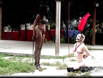 Lily and Nyomi, two horny lesbians, got out to play kinky. The brunette ebony milf is a very dominant bitch, while blonde Lily is more the obedient ty