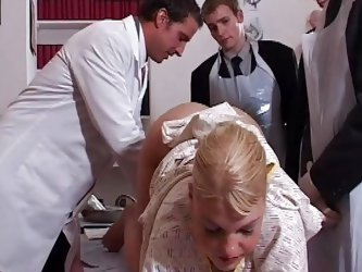Blonde babe Alicia needs a very rigorous medical exam and these guys are here for her. She stays there bent over and they probe her ass hole and pussy