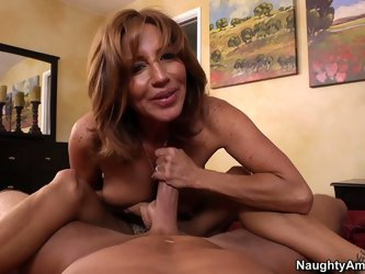 Gorgeous curly haired old prostitute pleases one more young cock. She smile while sucking it and works on that shaft with her delicious feet.