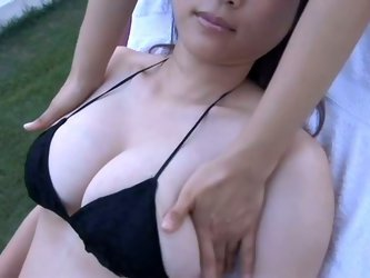 Heavenly cute milk skinned Japanese chick named Mami Nagaoka lies wearing tight black bikini while masseur rubs her chubby body with an extra care.