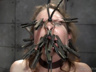 The mean master and dominatrix are placing clothespins on the slut slave's face. They want to see how many they can fit on there. She is bound an