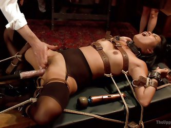 Veruca is tied to the table with rope and the master is increasing the speed on the fuck machine, that is pounding her cunt hole. In the other side of