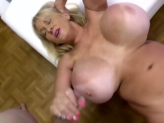 Mature blonde woman with massive milk jugs is getting her daily dose of fuck in the bedroom