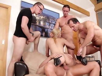 A blonde is in a gangbang in which she is getting fucked by several large men all at once. They are all sticking their dicks into her since her body i