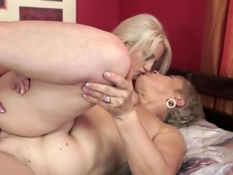 Nasty old woman and a cute young one are fucking in the bed