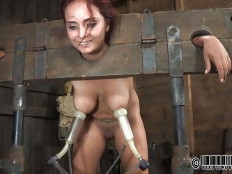 Ashley Graham is tied up in shackles with a milking machine attached to her huge breasts. She a dirty whore and these men punish her with humiliating